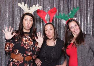 women wearing christmas props at photo booth