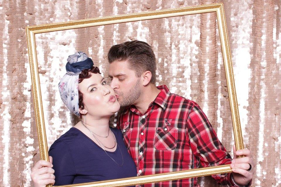 young couple making a fun pose in the confetti photo booth in idaho falls