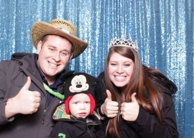 young family wearing props at birthday part photo booth